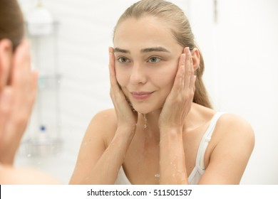 Young girl after washing her face water near the sink, removed makeup, home bathroom interior, view over shoulder. Reflected at the mirror, splashes running over her face. Beauty concept photo