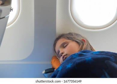 Young girl (age 05) sleeping in commercial airplane during a long distance air travel flight.