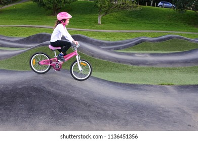 Young girl (age 08) rids bicycle on obstacle trek in a public park.