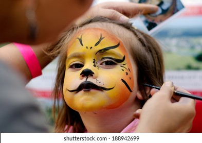 Young girl (age 4-5) getting her face painted like a lion by a face painting make up artist on Halloween Purim carnival holiday. Real people. Copy space