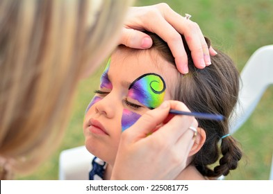 Young girl (age 5-6) getting her face painted like a butterfly by face painting artist. Real people. Copy space
