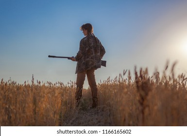 young girl with air rifle against field, silhouette of a girl with arms in hand, a girl standing in the field and holding a gun down, young girl shooting from the air rifle in the field