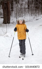 Young girl amateur sportsman skiing in winter snowy forest, full-length view