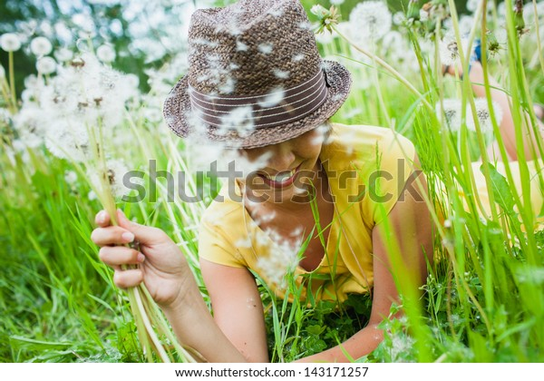 young girl among dandelions summer day