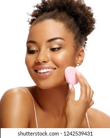 Young girl applying foundation on her face using makeup sponge. Photo of smiling african girl on white background