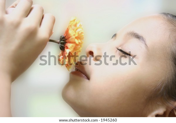A young girl appreciating the aroma from a single yellow chrysanthemum