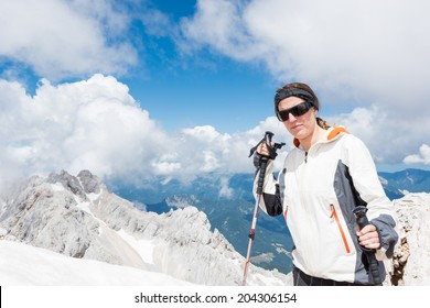 Young girl ascending a mountain with trekking poles