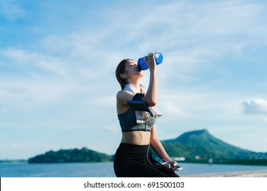 Young girl asian drinking protein shake nutrition and listen music after exercise running workout outdoor at beach seaside in summer for muscle building and slim fit body nice strong perfect.