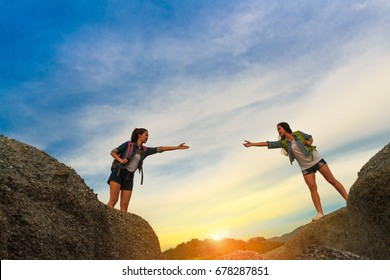 Young girl asian help friend with backpack holding hand across on the mountain in travel trip adventure
