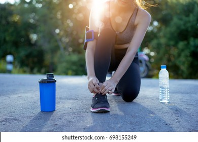 Young girl asian knelt down to do up his shoelaces with protein shake and water bottle on street after running exercise running workout street outdoor at mountain in summer for muscle building.