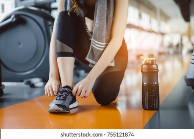 Young girl asian knelt down to do up his shoelaces with protein shake at fitness gym after running exercise workout for cardio and muscle building.