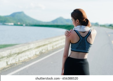 Young girl asian shoulder pain after exercise running and walking workout street outdoor at mountain beach seaside in summer for muscle building and slim fit body nice perfect strong.