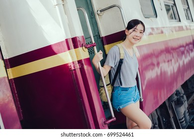 Young girl asian tourist take the train with backpack going to travel scenery town tour around at train station platform for take the rest