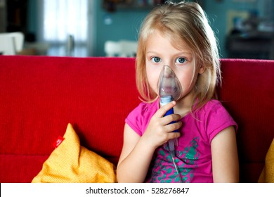 Young girl with asthma problems making inhalation with mask on her face