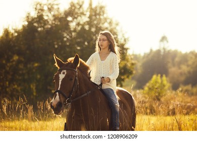 Young girl astride a sorrel horse in a field