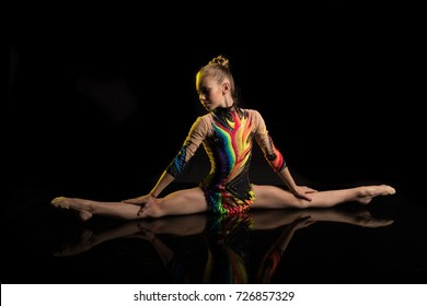 A young girl athlete gymnast performs acrobatic elements on a black background in a yellow scenic light.