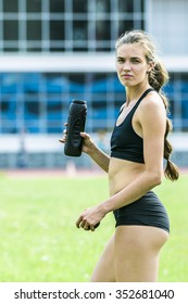 young girl athlete is with sport drink during training stadium. slim and beautiful body. beautiful face