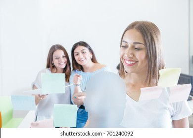 Young girl attaching stickers on wall of office with two cheerful coworkers on background.