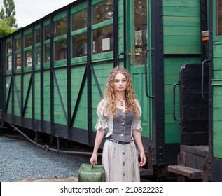 young girl with an attractive appearance with green suitcase standing on the railway station ready for the road, long curly blond hair falling on her shoulders