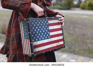 Young girl in the autumn park in the old coat standing with a suitcase like an American flag, fashion, style