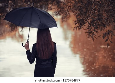 Young girl in autumn in rainy weather