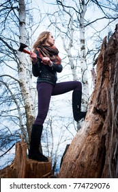 Young girl with axe, outdoors, early spring day.