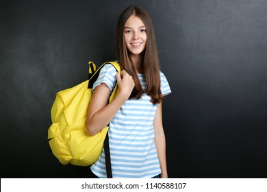 Young girl with backpack on blackboard background