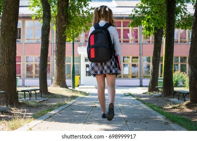 Young girl with a backpack standing in front of school, beginning of school year