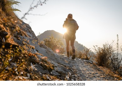 Young girl with backpack walking on the mountains path in the sunlight