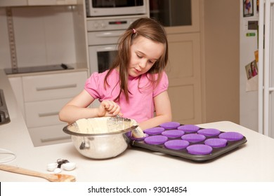 A young girl is baking cupcakes in their kitchen at home.
