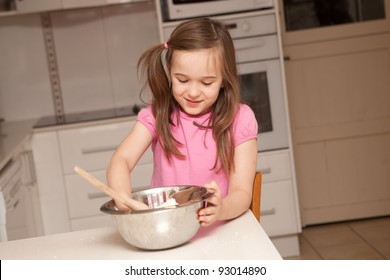 A young girl is baking cupcakes in their kitchen at home