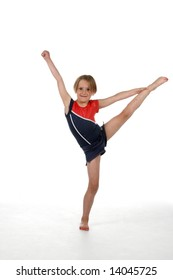 young girl balancing on one leg with the other one up in the air.