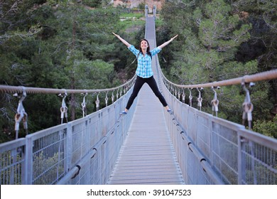 Young girl balancing on a railings of  suspension bridge through the forest in Haifa, Israel. challenge and win, Active life-stile concept. Young woman crossing the chasm on the rope pendant bridge