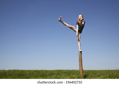 Young girl balancing outdoors on a trunk of a tree