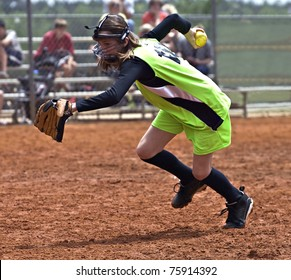 A young girl with ball in hand racing to make an out in a softball game.
