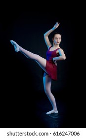 Young girl ballerina showing dance elements on a black background in blue scenic light