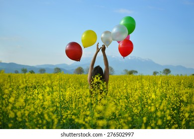 Young girl with balloons on canola field.