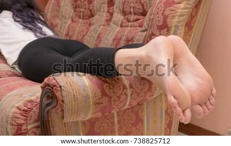 Young Girl In Bare Feet Soles On The Sofa