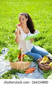 Young girl with a basket of vegetables and fruits at picnic outdoors