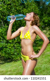 The young girl in a bathing suit drinking water in a park
