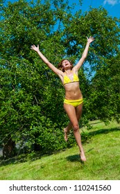 The young girl in a bathing suit jumping in park