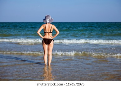 Young girl in a bathing suit and a striped hat is standing in the sea with her hands on her waist. Standing back
