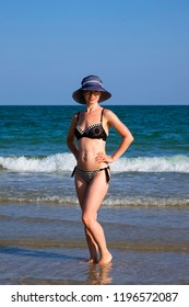 Young girl in a bathing suit and a striped hat is standing in the sea with her hands on her waist