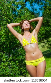 The young girl in a bathing suit sunbathes in park