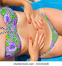 The young girl with a beautiful body sunbathes on a beach in a colorful  bathing