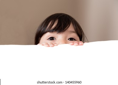 Young girl with beautiful eyes peeking over edge of table, white copy space below
