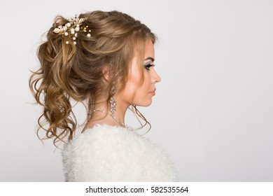 Young girl with beautiful hairstyle on a gray background