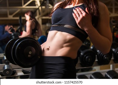 young girl with a beautiful press holding a dumbbell in the gym