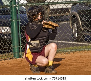 A young girl behind home plate watching intently ready to make a play.