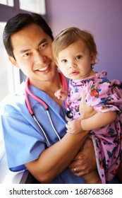 Young Girl Being Held By Male Pediatric Nurse